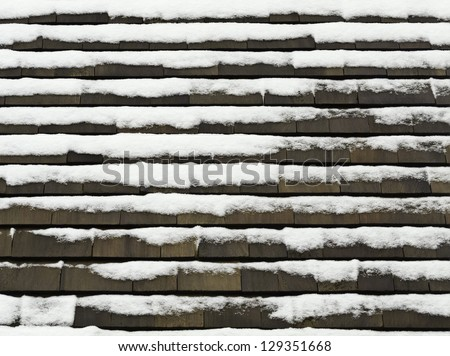 Winter at a glance: Roof with cedar shakes and snow - stock photo