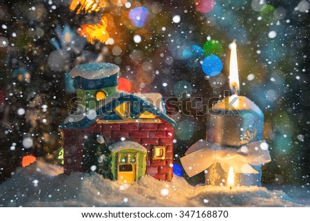 Winter background. Christmas background. Christmas house and candle. Close-up. Night Photography.