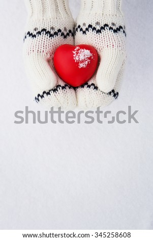 Winter background, close up of little girls hands holding red rubber heart with copy space - stock photo