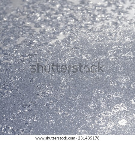 Winter background from frost and ice on frozen window. Colored in silver or grey tone. Selective focus with blur edges of image - stock photo