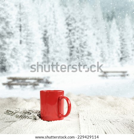 winter background of wooden old table with landscape of park in snow and warm red mug  - stock photo