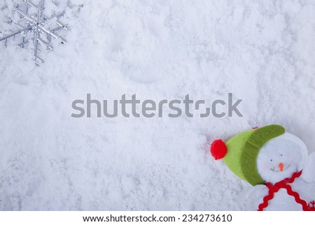 Winter background: snow, big snow flake or star and a decorated snowman. - stock photo