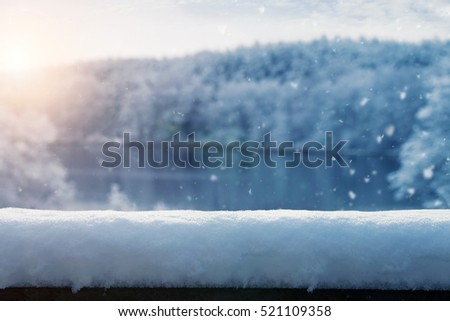 Winter background, snow falling over frozen lake landscape with copy space