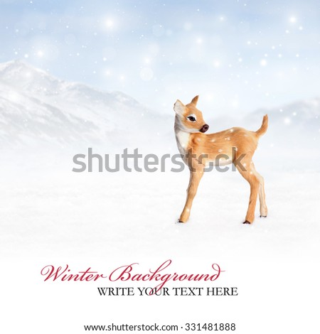 Winter background with a reindeer in a landscape with snow and mountains. Snowflakes are falling from the sky