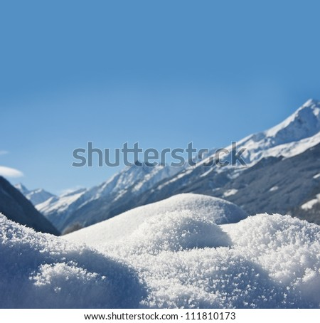 winter background with snow texture close up and mountains background