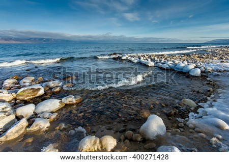 Winter beach, with rocks in the ice and the icicles, lake Baikal in winter - stock photo