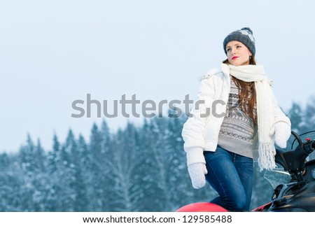 Winter, beautiful woman and a snowmobile, horizon format - stock photo