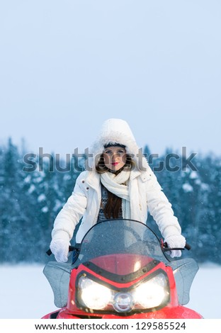 Winter, beautiful woman and a snowmobile, vertical format - stock photo