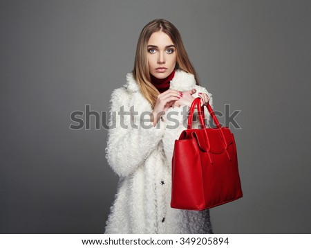 Winter beautiful Woman in Fur Coat. Beauty Fashion Model Girl. luxury stylish blond girl with red Handbag. Shopping - stock photo