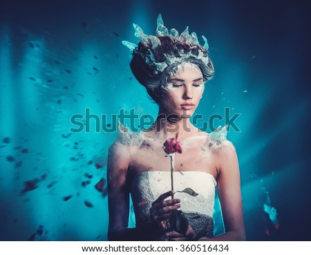 Winter beauty fantasy woman portrait. Beautiful young model girl and blast of frozen rose. - stock photo