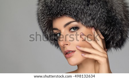 Winter beauty fashion. Beautiful face girl with trendy fur hat gesturing. Emotions. Professional makeup and manicure. High fashion portrait on grey background.  hand near the face