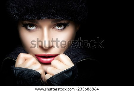 Winter Beauty Fashion. Closeup of gorgeous young woman wearing trendy fur hat and mittens with hands on chin while looking at camera sensually. High fashion portrait isolated on black with copy space. - stock photo
