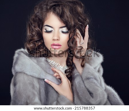 Winter Beauty fashion girl model in mink fur coat, makeup and long wavy hair style isolated on black