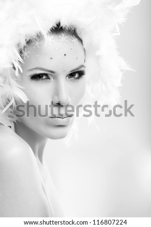 Winter beauty portrait of serious woman in white feather cap and rhinestones.