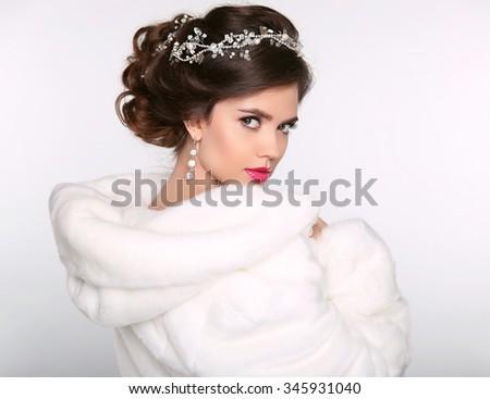 Winter beauty woman in white fur coat. Fashion model portrait. Jewelry. Wedding hairstyle. Elegant female.  - stock photo