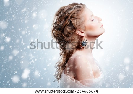 Winter beauty woman portrait with snowfall. Beautiful glamour model girl with Christmas fashion makeup and hairstyle showing trendy exclusive jewelry. Snow queen. Marie Antoinette style. - stock photo