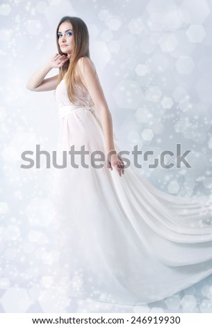 Winter beauty young woman studio photo on blue background - stock photo