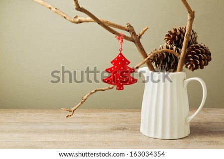 Winter branches with Christmas decoration tree in white jug - stock photo