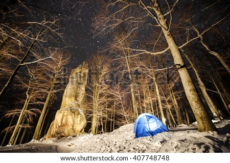 Winter camping. Base camp in a mountain forest next to amazing light painting rocky boulder. Night photography. Cold winter starry night in the mountains. - stock photo