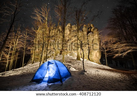 Winter camping in the mountains. Base camp in a mountain forest next to amazing light painting rocky cliffs/boulders. Night photography. - stock photo