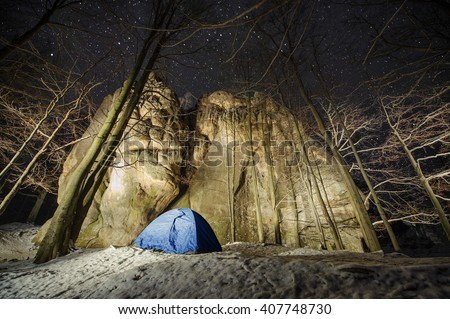 Winter camping in the mountains. Blue tent in a mountain forest next to amazing light painting rocky boulders. Night photography. Starry night - stock photo