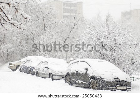 winter car during a snowfall in town - stock photo