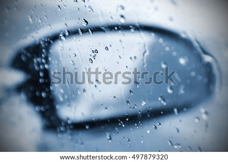 Winter car, the concept of winter car ride. Mirror and ice and water drops on the windscreen.
