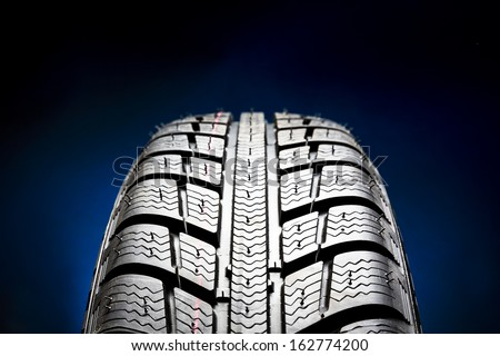 Winter Car tires close-up wheel profile structure on black blue background - stock photo