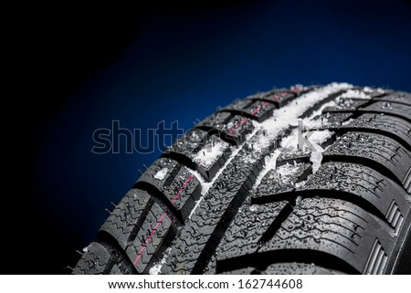 Winter Car tires with snow close-up wheel profile structure on black blue background - stock photo