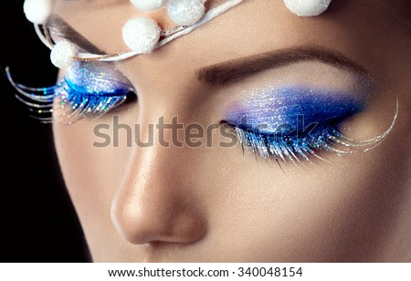 Winter Christmas eyes make up with glitter blue eyeshadows and false eyelashes. Party art model Woman makeup. Creative Girl Holiday Make-up. Snow Queen High Fashion Portrait over Black Background - stock photo