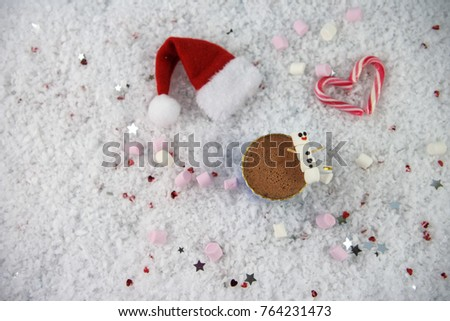 winter Christmas food and drink photography image of hot chocolate cup with marshmallows shaped as snowman with iced on smile and Santa hat all laid in snow sprinkled with small hearts and stars