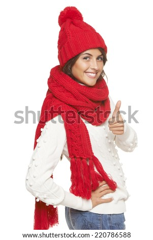 Winter, christmas, holidays concept. Smiling beautiful woman in red warm winter hat and scarf gesturing thumb up, over white background - stock photo