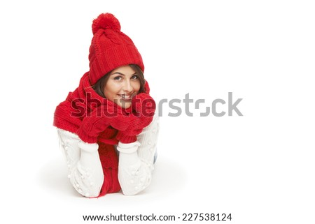 Winter, christmas, holidays concept. Smiling beautiful woman in red winter hat, scarf and mittens lying down over white background - stock photo