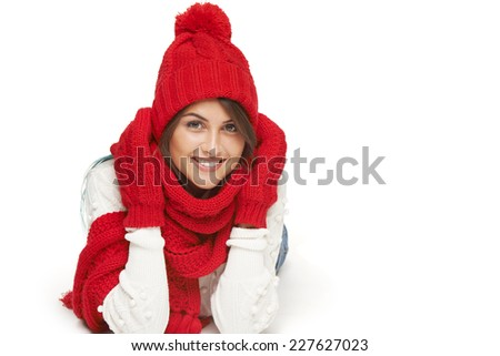Winter, christmas, holidays concept. Smiling beautiful woman in red winter hat, scarf and mittens lying down over white background