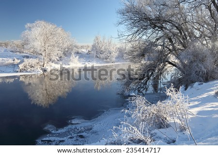 Winter christmas landscape with river and snow covered trees beautiful reflection in the water at very cold weather. Winter panorama at sunny day.