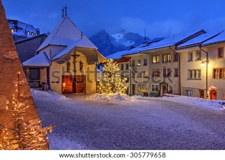 Winter (Christmas) night scene in the medieval town of Gruyeres, district of Gruyere, Fribourg canton, Switzerland, where the famous cheese bearing the name is made. - stock photo