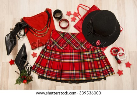 Winter Christmas sweater and plaid skirt with accessories arranged on the floor. Woman red outfit with matching hat, necklace, bracelet and nail polish lied down. - stock photo