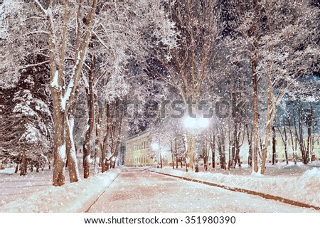 Winter city landscape - snowy night alley in the park in winter evening with a lot of frosty trees under falling snow and shining lanterns  - stock photo