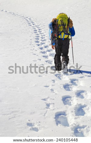 Winter climber follows a trail of foot steps on snowy mountain  - stock photo