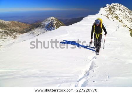 Winter climber walking on snowy mountain ridge in fine day - stock photo