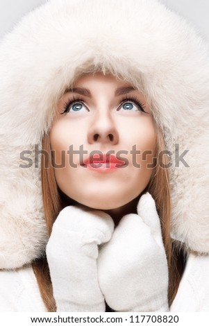 Winter close-up portrait of young beautiful woman  in white hat and white mittens - stock photo