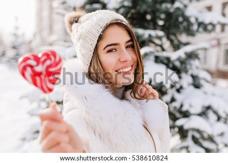 Winter closeup portrait charming joyful young woman in sunny winter morning with pink lollipop on street. White warm woolen knitted hat, enjoying cold weather, delicious. Happy time, positive emotions