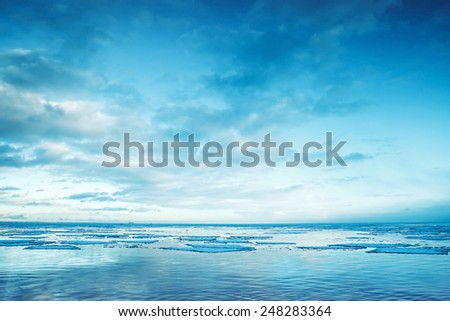 Winter coastal landscape with floating ice fragments on still sea water. Gulf of Finland, Russia. Blue toned photo filter effect - stock photo