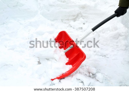 Winter concept. Woman hand with red shovel for snow removal - stock photo