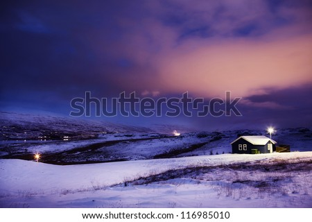 Winter Cottage in Snow with Dramatic Clouds at Night - stock photo
