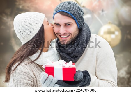 Winter couple holding gift against blurred christmas background - stock photo
