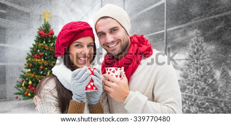 Winter couple holding mugs against home with christmas tree - stock photo