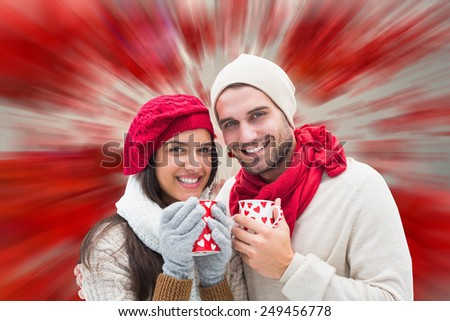 Winter couple holding mugs against love heart pattern