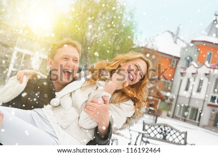 Winter couple piggyback in snow smiling happy and excited. Beautiful young couple at backyard of their house - stock photo