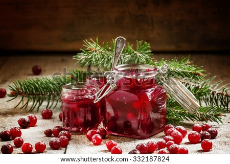 Winter cranberry sauce in glass jars with fresh cranberries, decorated fir branches and snow on the old wooden background, selective focus - stock photo